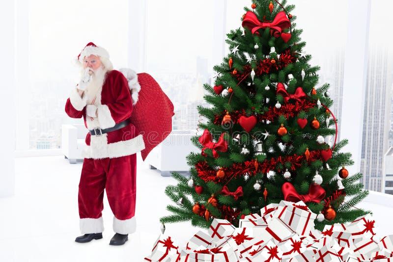 De Kerstman met vinger op lippen die zich dichtbij Kerstmisboom bevinden stock foto