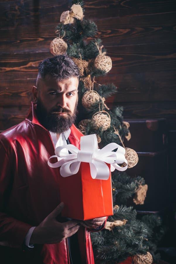De Kerstman in modern rood jasje Kerstboom op huis houten achtergrond De Kerstman met gift De Kerstmiswensen komen royalty-vrije stock afbeeldingen