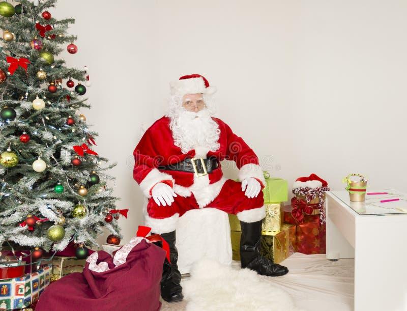 De Kerstman op de stoel in vakantiescène royalty-vrije stock afbeelding