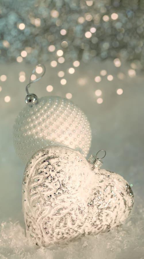 De Kerstman op een slee Glashart en een witte bal met parels op een sneeuw Vage grijze achtergrond van geel bokeh en licht royalty-vrije stock afbeelding