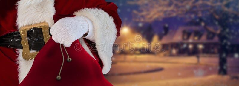 De Kerstman zijn zak houden die zich bevindt op de sneeuw witte straten met een huis op de achtergrond van afstandskerstmis stock foto