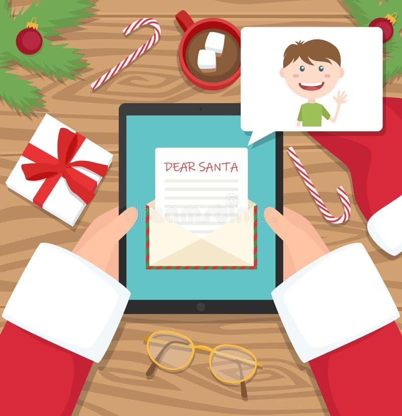 De Kerstman zit bij zijn werkplaatsbureau en ontvangt brief op zijn tablet van jonge jongen royalty-vrije stock foto