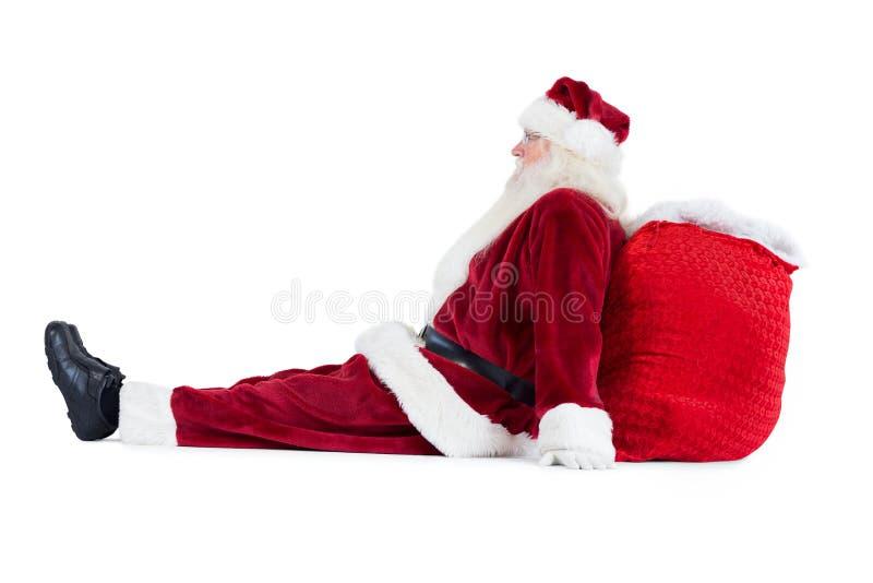 De kerstman zit geleund op zijn zak stock afbeelding