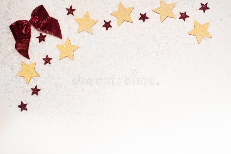 De Kerstmisachtergrond, met goud schittert sterren, rode boog, en sneeuw stock foto