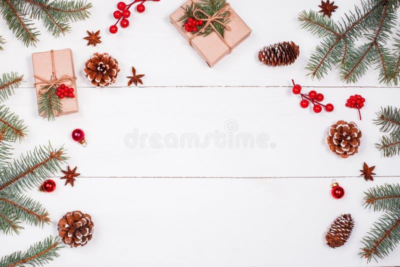 De Kerstmisachtergrond met Kerstmisgift, spar vertakt zich, denneappels, sneeuwvlokken, rode decoratie Kerstmis en gelukkig nieuw royalty-vrije stock fotografie