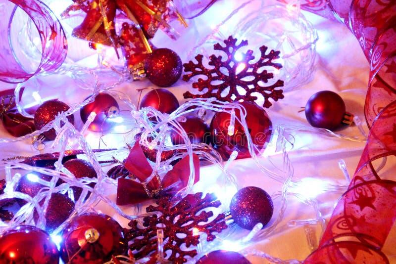 De Kerstmisachtergrond is verfraaid met lichten van slingers, fonkelende rode ballen, sneeuwvlok en decoratief stock fotografie