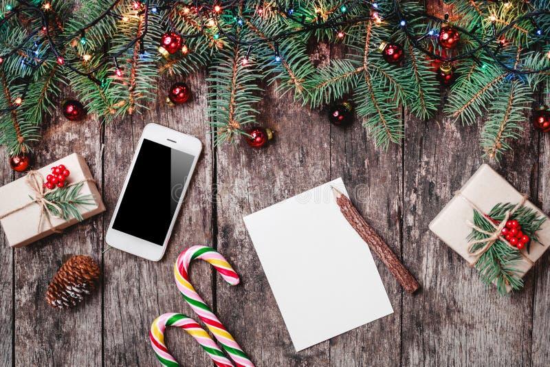 De Kerstmisbrief op houten achtergrond met mobiele telefoon, giften, suikergoed, Spar vertakt zich, rode decoratie stock afbeeldingen