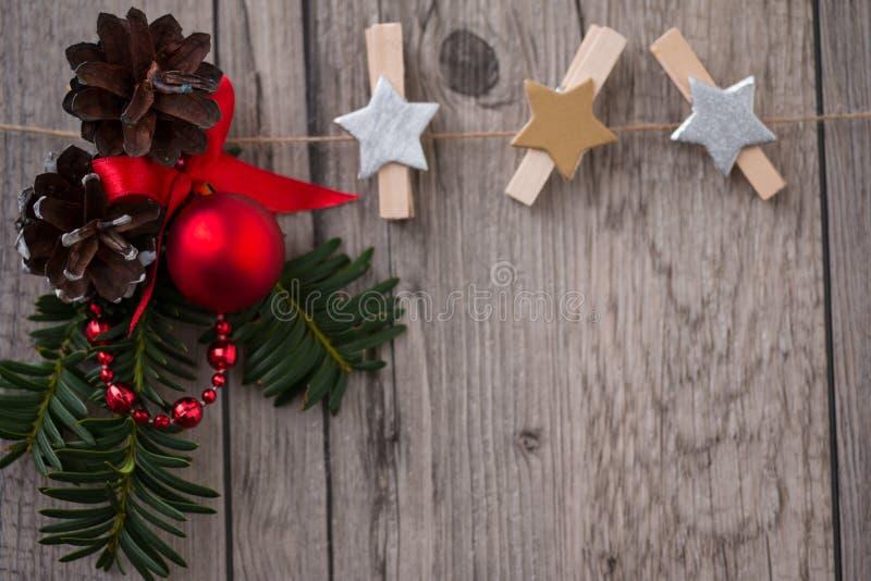 De Kerstmisdecoratie met altijdgroene boomtakjes, denneappel, rode bal en houten pinklemmen in vorm spelen mee royalty-vrije stock afbeelding