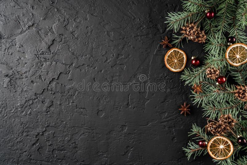 De Kerstmisdecoratie op vakantieachtergrond met Spar vertakt zich, denneappels, rode decoratie, kruiden Kerstmis stock foto
