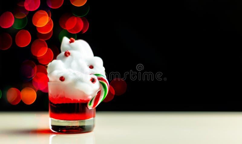 De Kerstmisdrank schoot in een geschoten glas op een bokehachtergrond, Kerstmisdecoratie op de bar, Kerstmispartij stock afbeelding