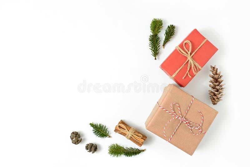 De Kerstmisgiften in ambacht bruin en rood die document worden verpakt met spar en pijnboom wordt vertakt zich en kegels op witte stock fotografie