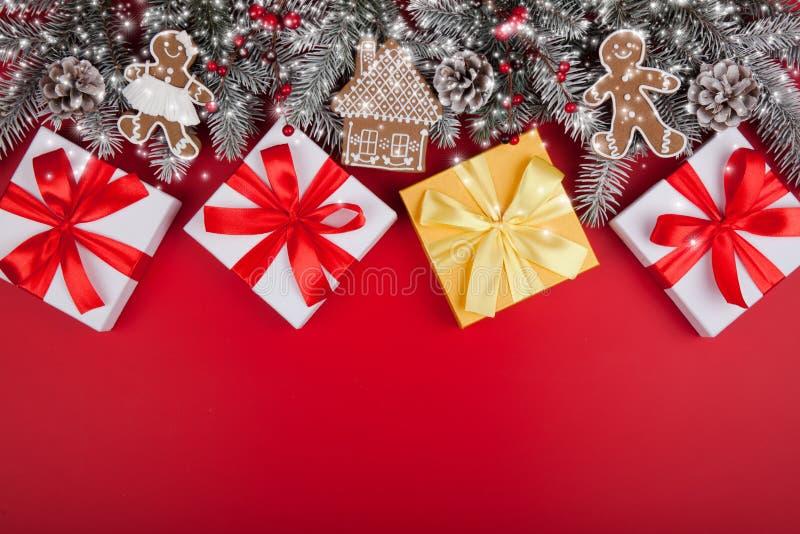 De Kerstmisgiften stelt op rode achtergrond voor Witte en gouden de giftdozen van de sneeuwspar met lintbogen en feestelijk stock foto