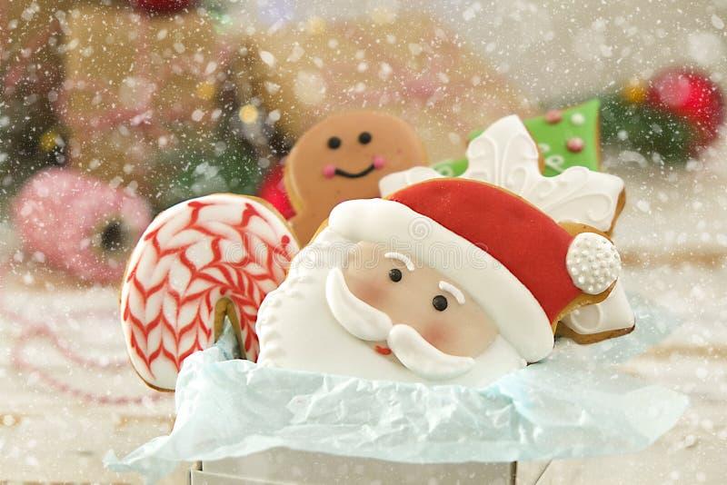 De Kerstmiskoekjes in een vakje met giften, lichten en spar vertakt zich op witte uitstekende houten lijst Sneeuweffect, bokeh stock afbeeldingen