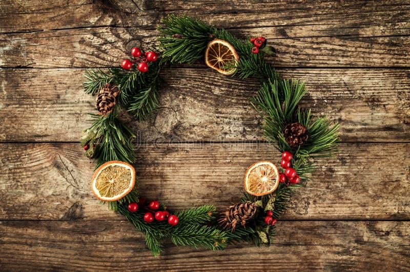 De Kerstmiskroon van Spar vertakt zich, kegels, rode decoratie op houten achtergrond met sneeuwvlokken royalty-vrije stock afbeelding