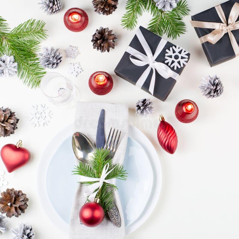 De Kerstmislijst die met platen, tafelzilver plaatsen, stelt en decoratie voor Hoogste mening stock afbeeldingen