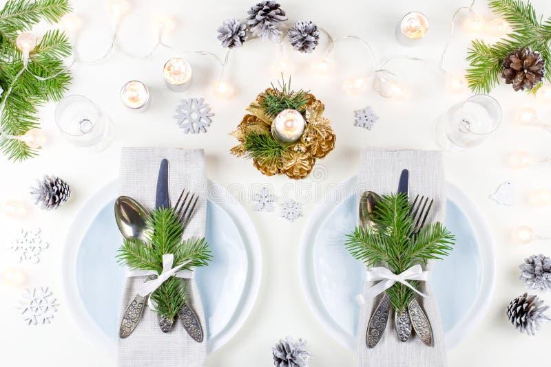 De Kerstmislijst die met platen, tafelzilver plaatsen, stelt en decoratie voor Hoogste mening stock foto