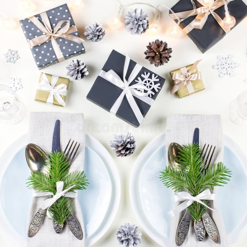 De Kerstmislijst die met platen, tafelzilver plaatsen, stelt voor, schouwt en decoratie stock afbeelding