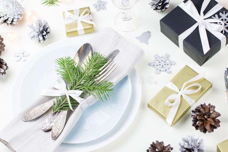 De Kerstmislijst die met platen, tafelzilver plaatsen, stelt voor, schouwt en decoratie stock foto