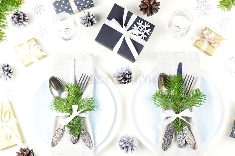 De Kerstmislijst die met platen, tafelzilver plaatsen, stelt voor, schouwt en decoratie stock fotografie