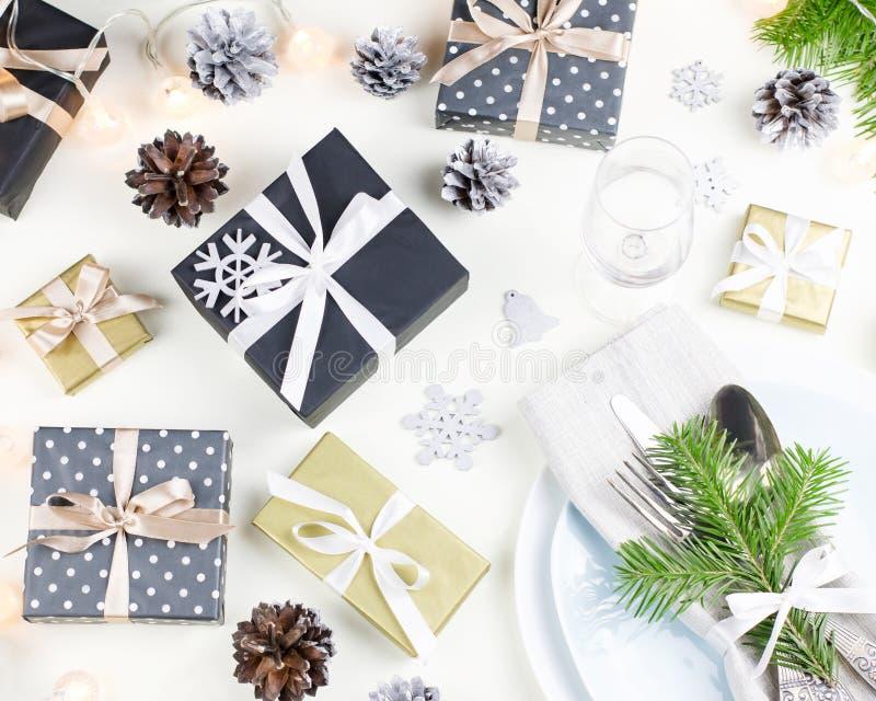 De Kerstmislijst die met platen, tafelzilver plaatsen, stelt voor, schouwt en decoratie royalty-vrije stock foto
