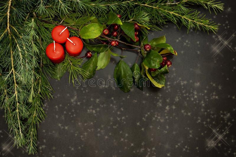 De Kerstmisornamenten met kleine rode bessen, heldere ballen, rode kaarsen en een pijnboom vertakken zich stock afbeelding