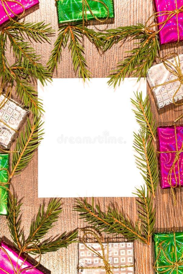 De Kerstmissamenstelling met giftvakjes, spar vertakt zich en leeg verticaal blad van document op houten raad, stock foto