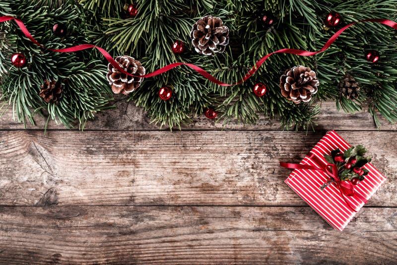 De Kerstmisspar vertakt zich op vakantie houten achtergrond met giftdozen, denneappels, rode decoratie royalty-vrije stock afbeeldingen