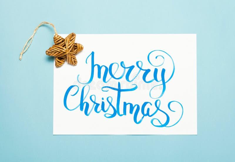 De Kerstmisvlakte legt: het van letters voorzien tekst` Vrolijke Kerstmis ` en uitstekende houten ster op blauwe achtergrond royalty-vrije stock afbeeldingen