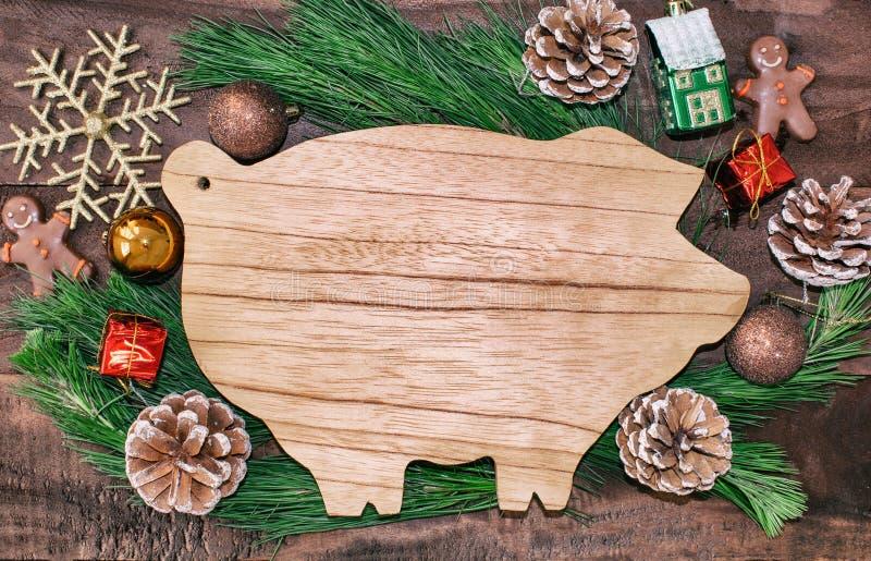 De Kerstmisvoorbereidingen, scherpe raad in de vorm van varkens, spar vertakt zich, kegels en decoratie Nieuwjaar van het varken  stock afbeelding