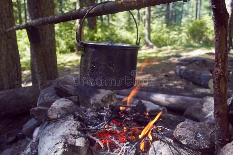 De ketel kookt op de brand in het bos in het marcheren van een steelpan voorbereidend voedsel Avonturentoerisme, het kamperen, di stock afbeeldingen
