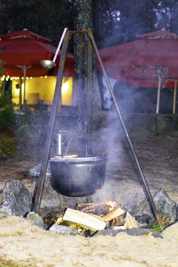 De ketel op een houten dwarsligger hangt over een brand op bos stock fotografie
