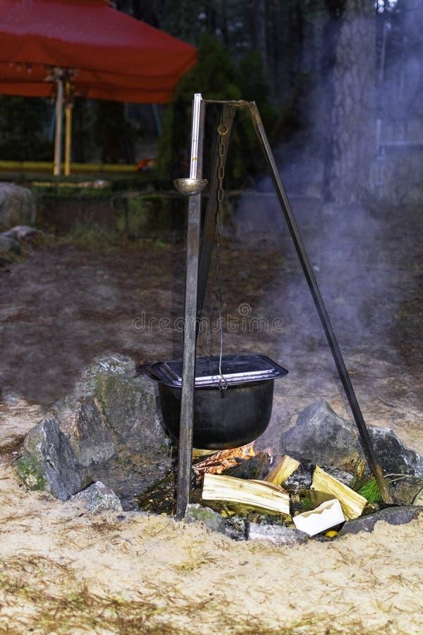 De ketel op een houten dwarsligger hangt over een brand op bos stock afbeelding