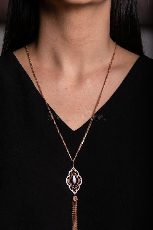 De ketting van vrouwen van roze goud met een tegenhanger met een zwarte steen in het midden, met het egging van het hangen rond z stock foto's