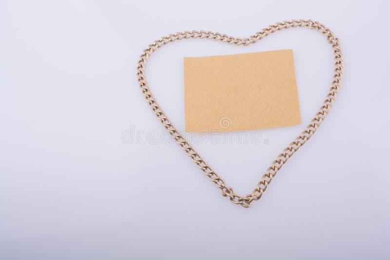 De ketting vormt een hartvorm met een leeg document stock afbeeldingen