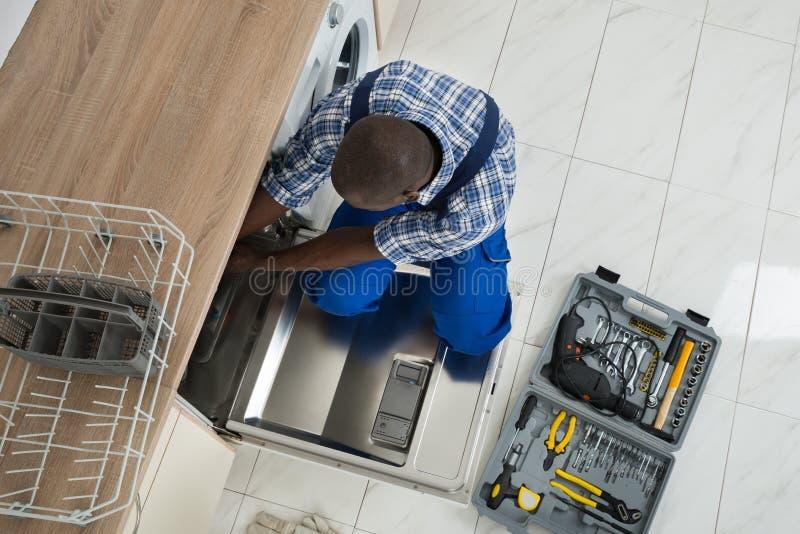 De Keuken van herstellerrepairing dishwasher in stock afbeelding