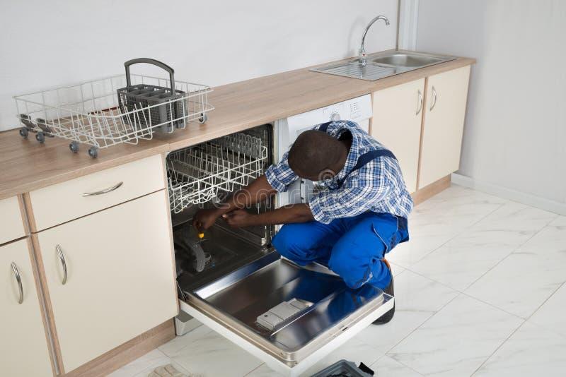 De Keuken van herstellerrepairing dishwasher in royalty-vrije stock afbeeldingen
