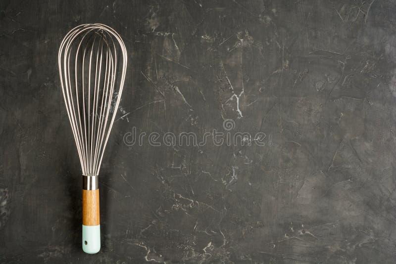 De keukendraad zwaait Eierenklopper op de donkere concrete achtergrond met exemplaarruimte Vlak leg achtergrond stock afbeeldingen