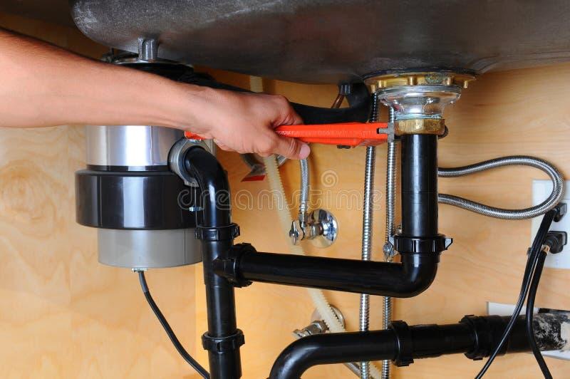 De Keukengootsteen van loodgieterusing wrench under royalty-vrije stock fotografie