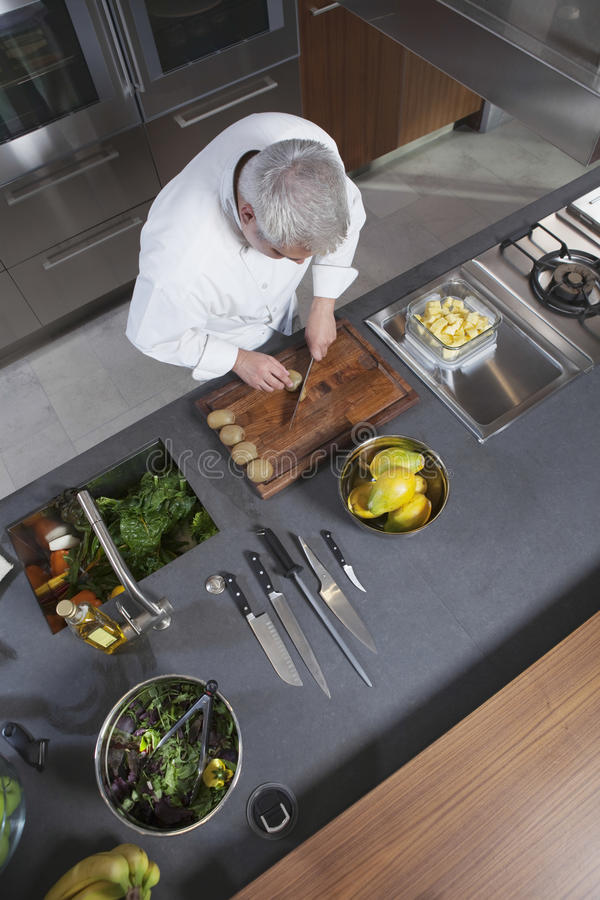 De Keukenteller van chef-kokChopping Kiwi On Board At Commercial stock fotografie