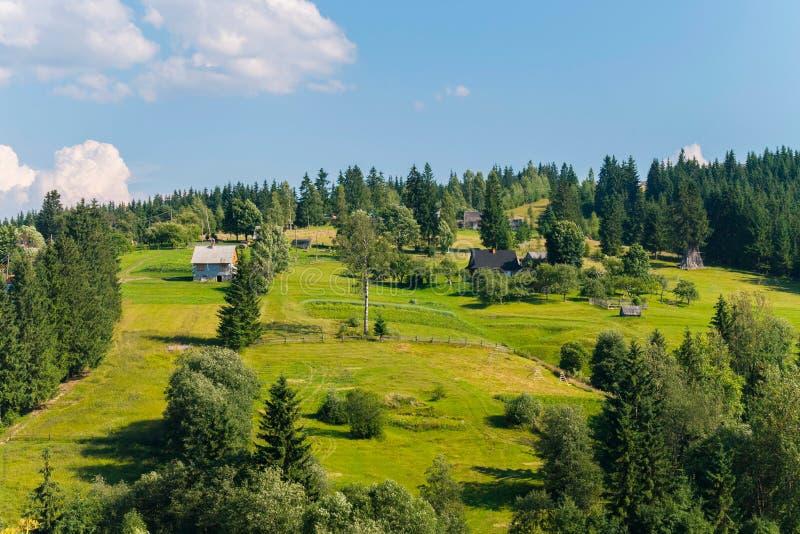 De keurige kleine landelijke huizen tegen de achtergrond van een groene berg hellen en blauwe hemel royalty-vrije stock afbeeldingen