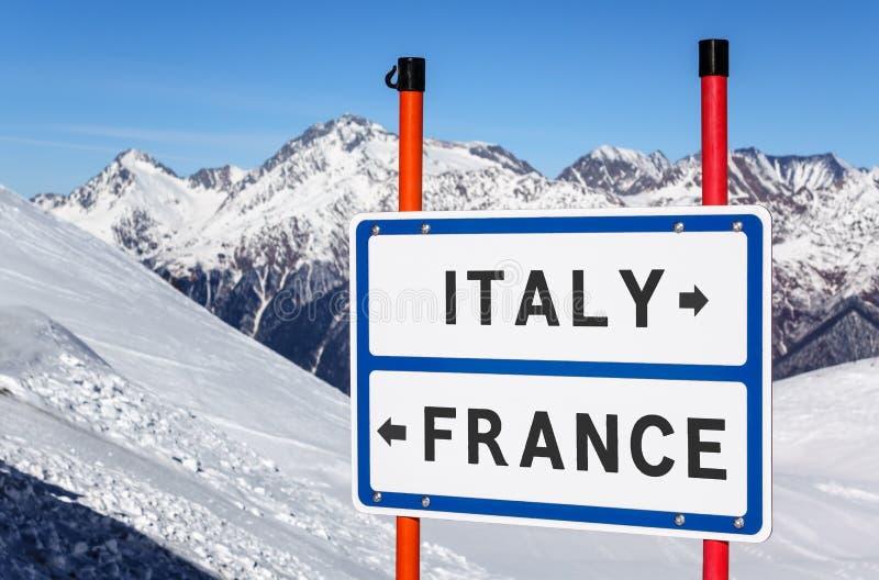 De keus van Italië of van Frankrijk aan ski of snowboard Informatieteken op de pieken van de de winterberg onder blauwe hemelacht stock foto's