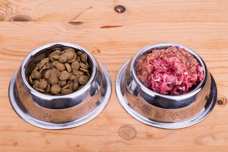 De keus van ruw vlees of verbrokkelt hondevoer in kom stock afbeeldingen