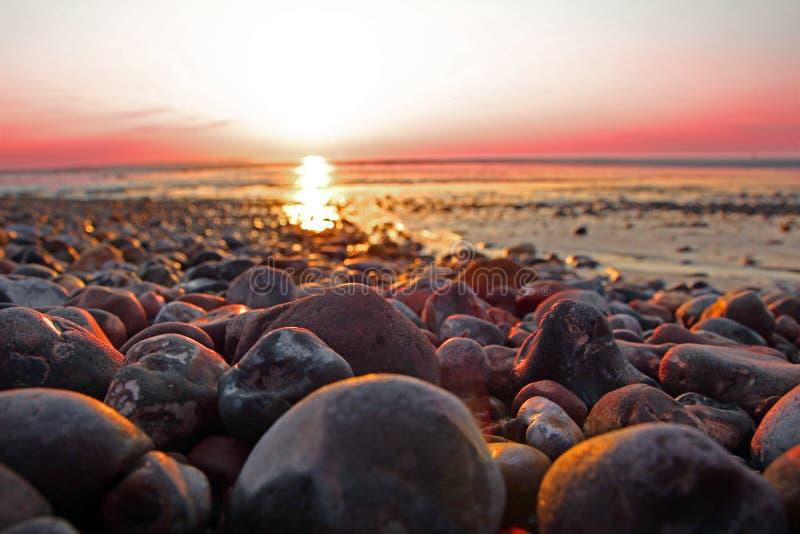 De kiezelstenen van het zonsondergangstrand stock foto's