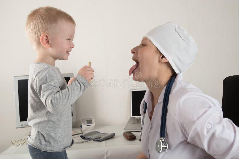 De kind ` s arts onderzoekt patiënten in zijn bureau De gelukkige kinderen houden zeer van een goede pediater Sluit omhoog van ee stock afbeelding