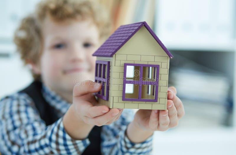 De kind` s hand houdt het huis Familie, aankoop van huisvesting, flat, hypotheek, overerving stock foto's