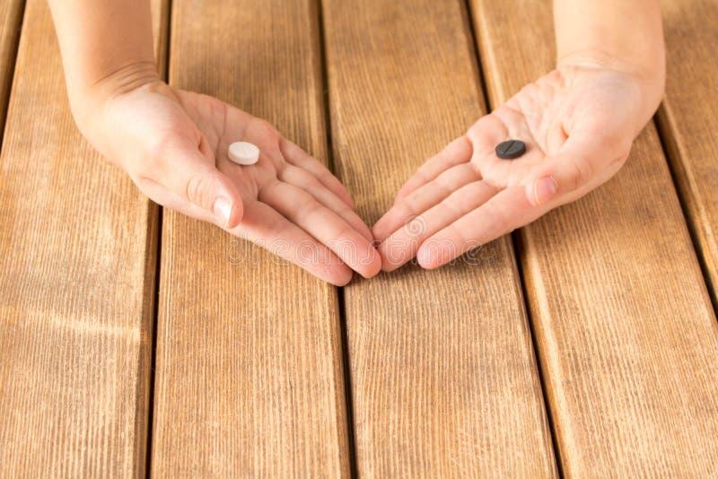 De kind` s hand met zwart-witte pillen op houten achtergrond royalty-vrije stock fotografie