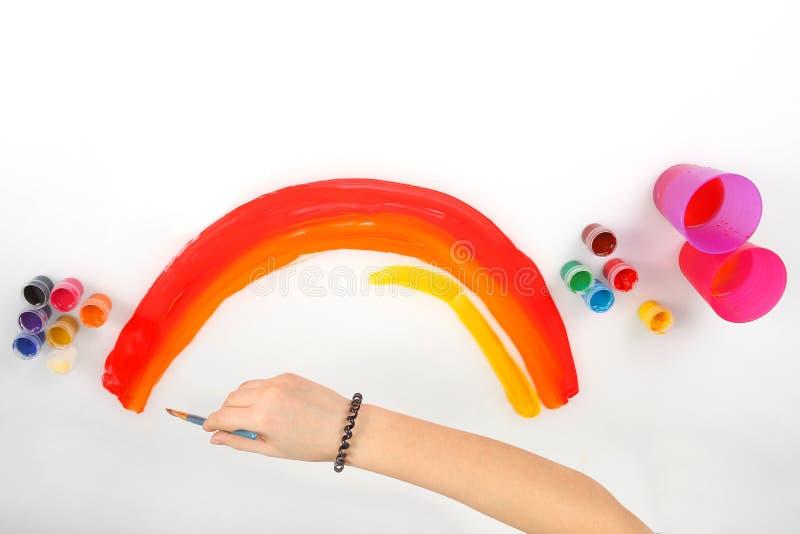 De kind` s hand trekt een regenboog op een witte achtergrond stock afbeeldingen