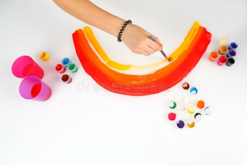 De kind` s hand trekt een regenboog op een witte achtergrond stock foto