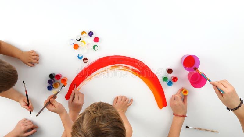 De kind` s handen trekt een regenboog op een witte achtergrond royalty-vrije stock foto