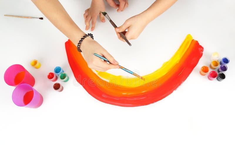 De kind` s handen trekt een regenboog op een witte achtergrond stock afbeeldingen